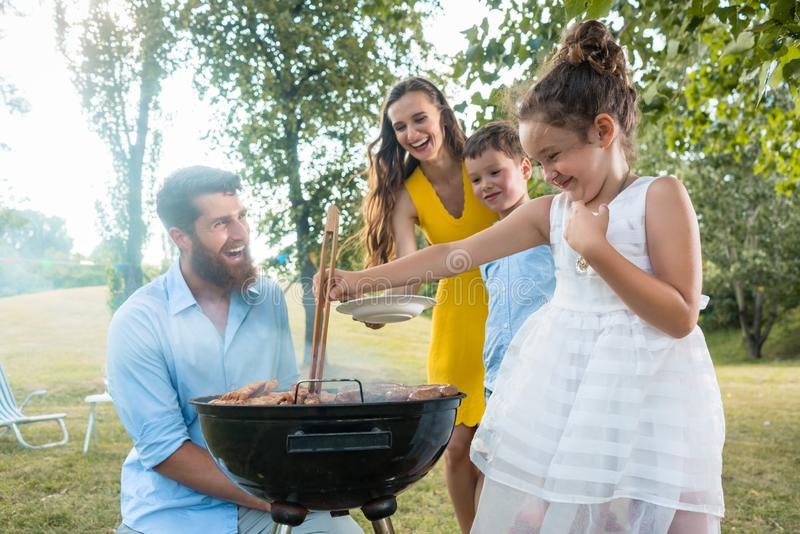 Cute funny girl preparing meat on BBQ charcoal grill. Cute funny girl using wooden tongs while preparing meat on the BBQ charcoal grill in front of her father royalty free stock images