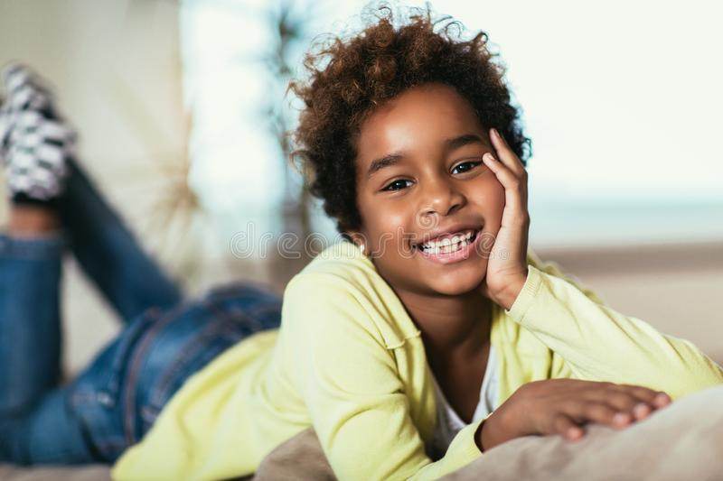 Little african american girl looking at camera, smiling mixed race child posing for portrait at home royalty free stock images