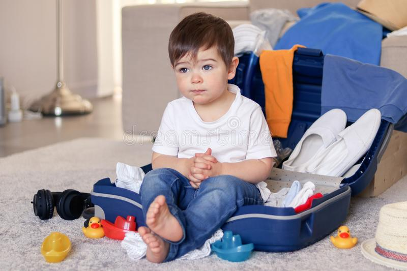 Cute funny little baby boy having rest siiting in blue suitcase tired of packing clothes and toys for vacation. royalty free stock images