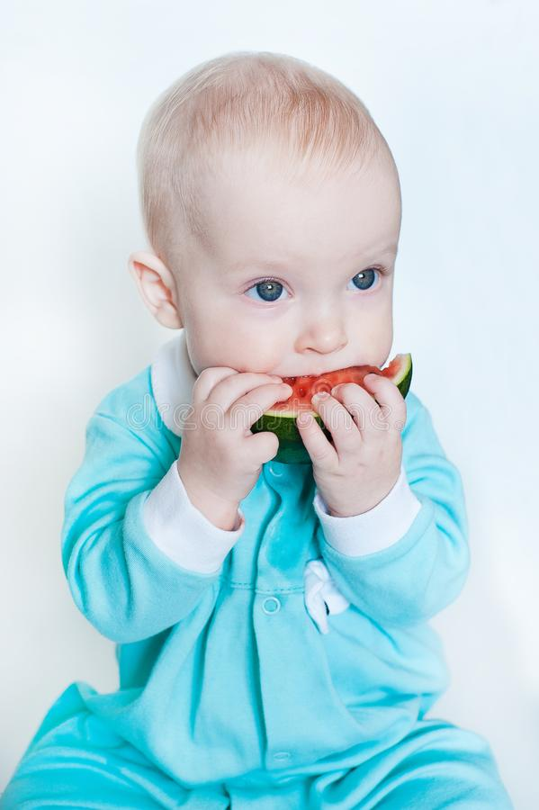 Cute funny little baby girl in turquoise rompers with watermelon on white background. stock photos
