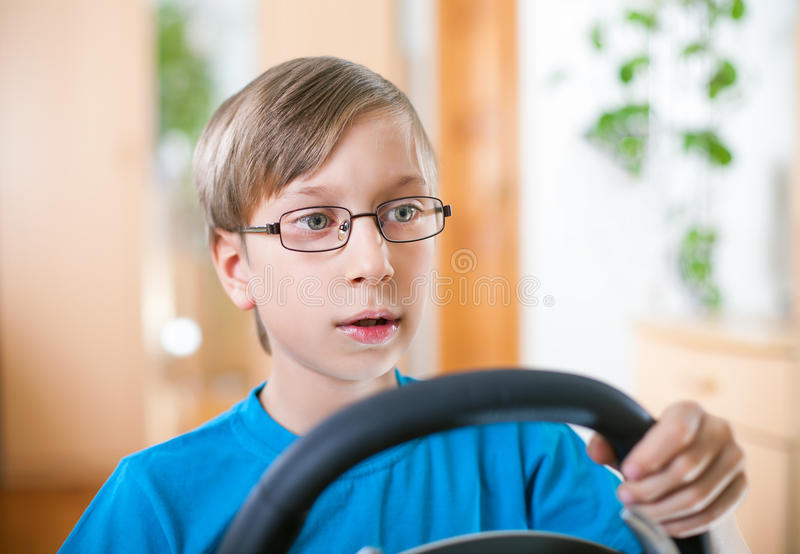 Cute funny little child playing at computer driving stock photos
