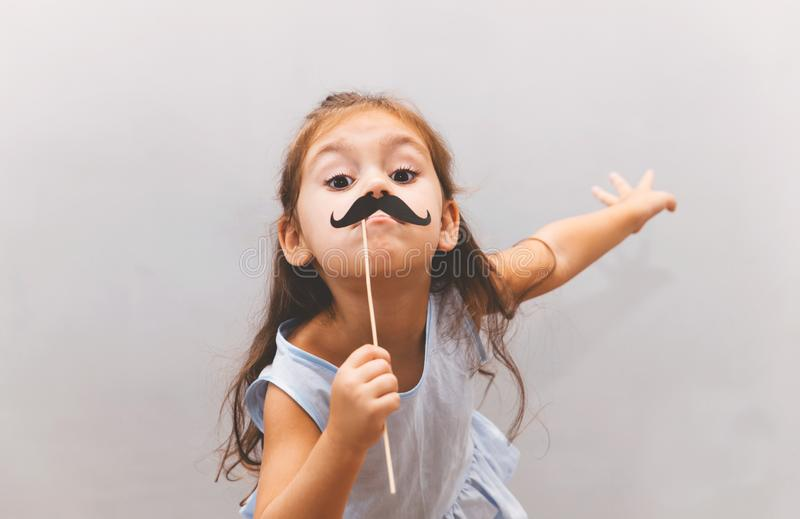 Cute funny little girl wearing paper mustache stock images
