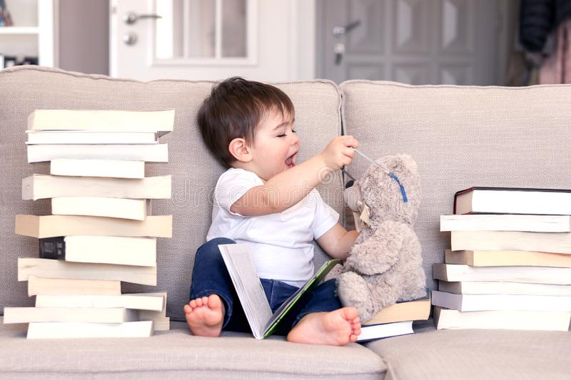 Cute funny playful little baby boy reading book and playing with teddy bear toy putting glasses on it sitting on sofa between pile royalty free stock image