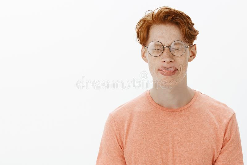 Cute and funny redhead man with freckles and stylish haircut in round glasses sticking out tongue, trying to roll it stock images
