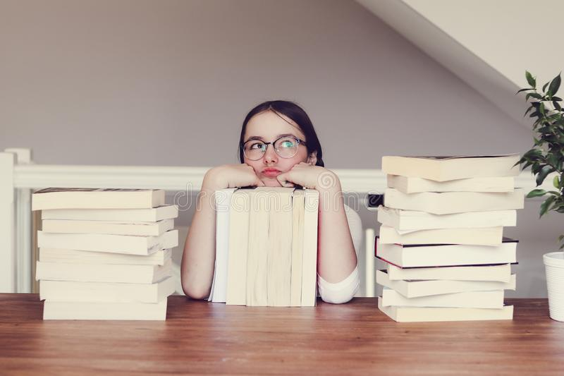 Cute funny tween girl in glasses sitting a table with pile of books looking sceptically and daydreaming of holidays. royalty free stock images