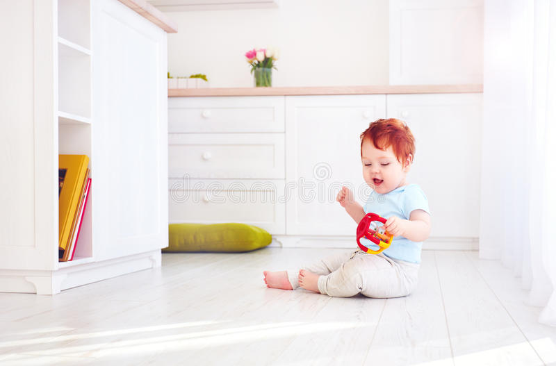 Cute ginger baby boy playing with toys in bright kitchen, at home stock photography