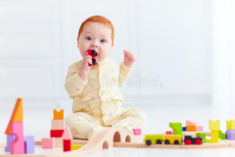 Cute ginger baby playing with toy railway road at home. Tasting wagon. Cute ginger baby boy playing with toy railway road at home royalty free stock photo