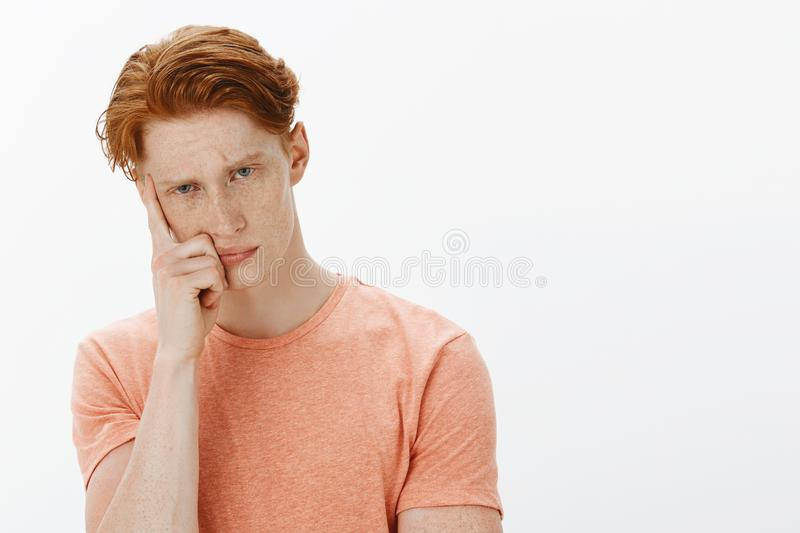 Cute ginger man trying to learn foreign language sitting intense and serious in class, cannot focus or understand royalty free stock photography