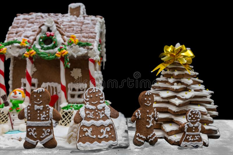 Cute gingerbread family near snow-covered homemade gingerbread h. Ouse and Christmas tree. Mockup for seasonal offers and holiday post card stock photo