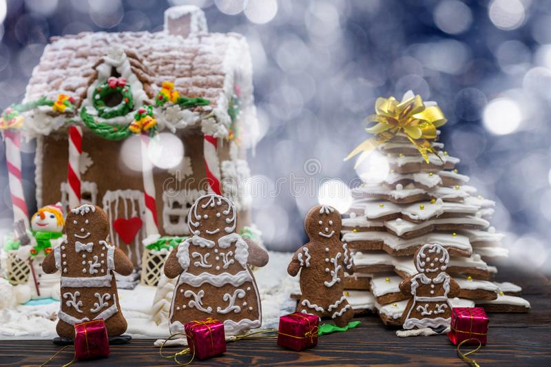 Cute gingerbread family with small red gifts near snow-covered h. Omemade gingerbread house and Christmas tree. Mockup for seasonal offers and holiday post card stock photography