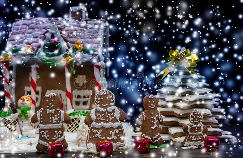 Cute gingerbread family with small red gifts near snow-covered h. Omemade gingerbread house and Christmas tree during the snow. Mockup for seasonal offers and royalty free stock image