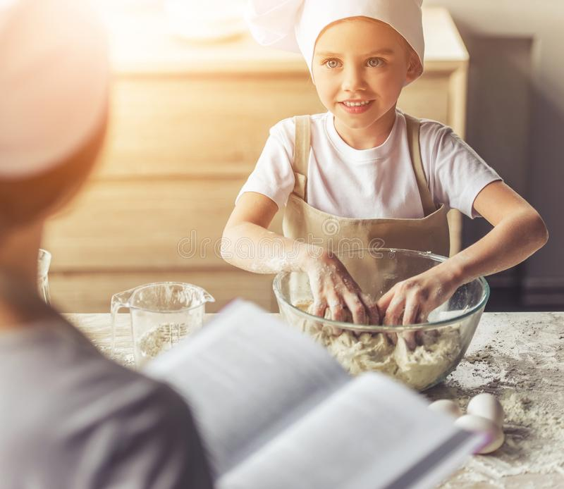 Cute Girl in Apron and Chef Hat Looking at Her Mom stock image