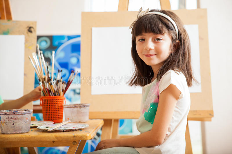Cute girl in art class. Beautiful little brunette ready for her drawing lesson at school stock photo