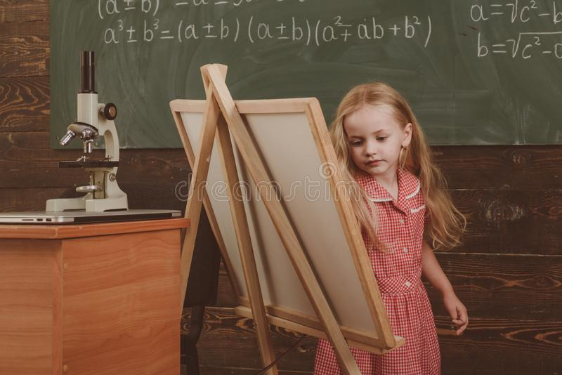 Cute girl artist painting picture on canvas on easel. Little child learn drawing on studio easel, vintage filter royalty free stock images