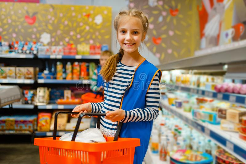 Cute girl with basket playing saleswoman, playroom stock photography
