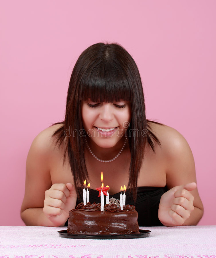 Cute girl with birthday cake. Cute girl looking at her chocolate birthday cake royalty free stock photos