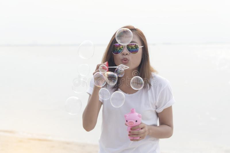 Cute girl blowing bubble on the beach stock photos