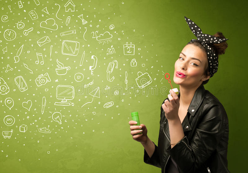 Cute girl blowing hand drawn media icons and symbols. On green background stock image