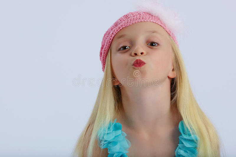 Cute girl blowing kiss. Portrait of cute young blond girl in pink hat blowing kiss; white studio background and copy space royalty free stock photo