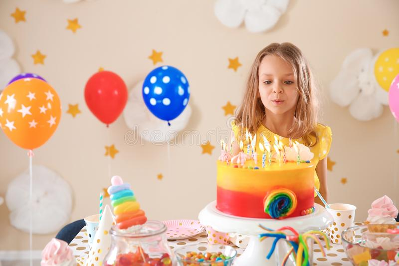 Cute girl blowing out candles on her birthday cake indoors. Cute little girl blowing out candles on her birthday cake indoors royalty free stock photo