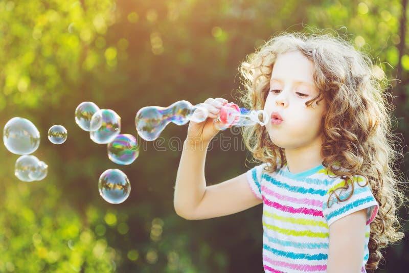 Cute girl blowing soap bubbles, close-up portrait. stock photos