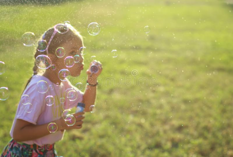 Cute girl blowing soap bubbles, bubbles focused royalty free stock images