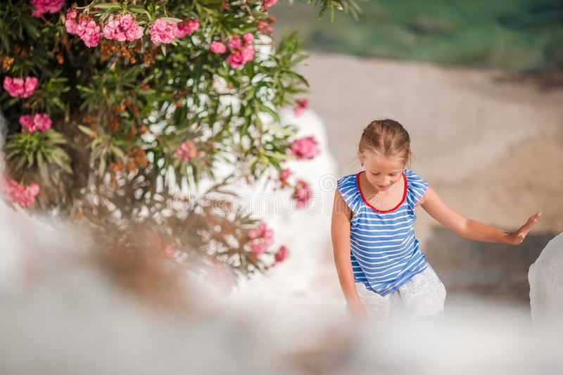 Cute girl in blue dresses having fun outdoors on Mykonos streets royalty free stock images