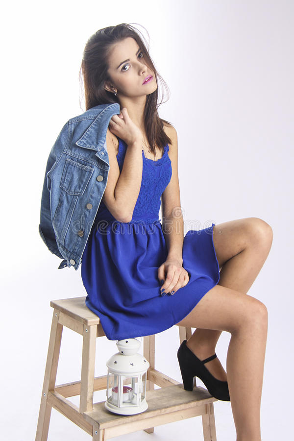 Cute girl in blue jacket on wooden chair royalty free stock photos