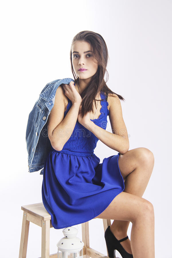 Cute girl in blue jacket on wooden chair stock photos