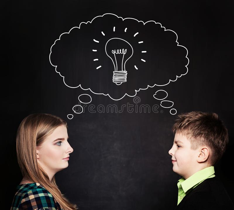 Cute Girl and Boy with Lightbulb at the Blackboard stock photography