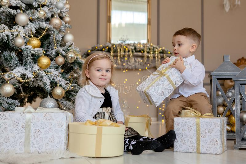Cute Girl and boy opening Xmas presents. Children under Christmas tree with gift boxes. Decorated living room with traditional stock images