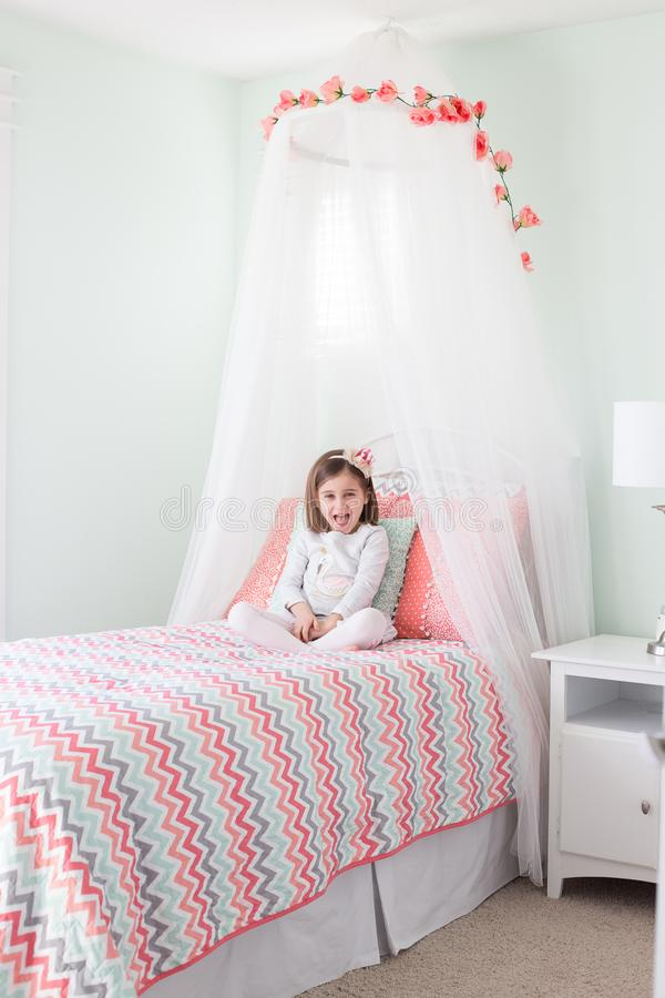 Cute girl in canopy bed royalty free stock photo