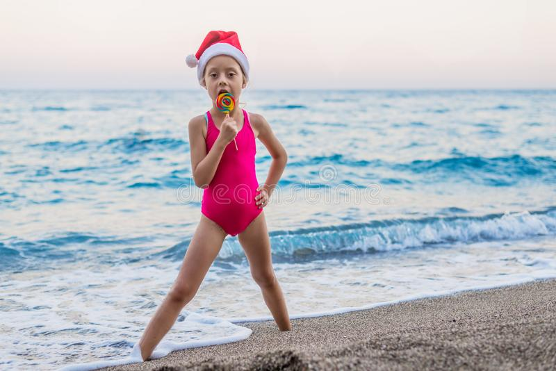 Cute girl celebrating New Year and Christmas on the beach in a hat of Santa Claus, free space. Christmas background, winter holidays in tropical countries stock photo