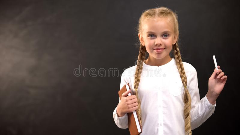 Cute girl with chalk and book smiling at camera, private school advertisement royalty free stock image