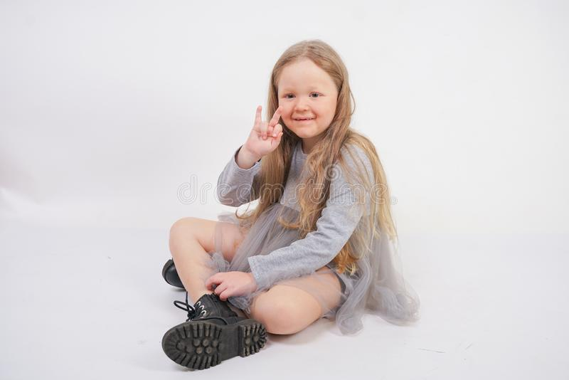 Cute girl child with long blond hair sitting on the floor and yawns sweetly, stretching her hands in different directions on white royalty free stock images