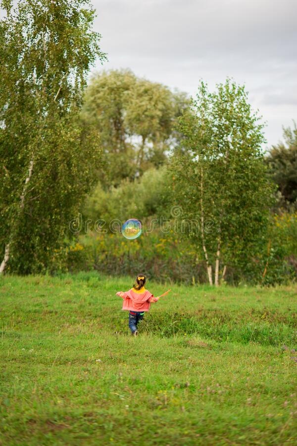 Cute girl child 4-5 years old in a pink sweater, a yellow T-shirt and jeans catches giant soap bubbles in nature.  royalty free stock photos