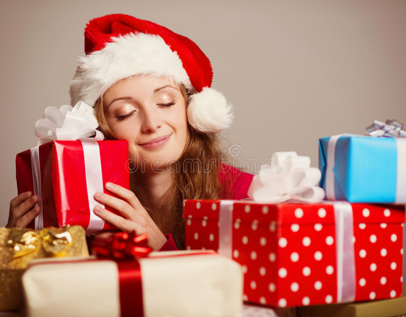 Cute girl with christmas presents. Smiling girl in a christmas hat with colourful seasonal gifts stock images