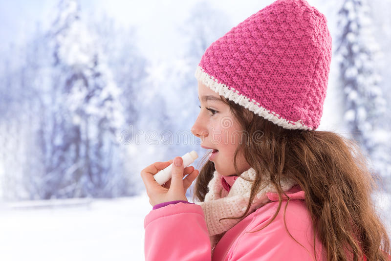 Cute girl clothes applying lip balm. Teen girl taking care od her lip with balm in winter stock photo