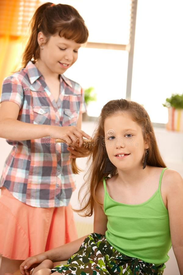 Cute girl combing friend s hair