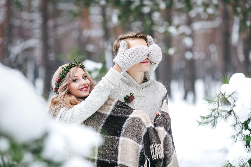 Cute girl covering boyfriend`s eyes by her knitted mittes. Winter wedding. Artwork. stock photo