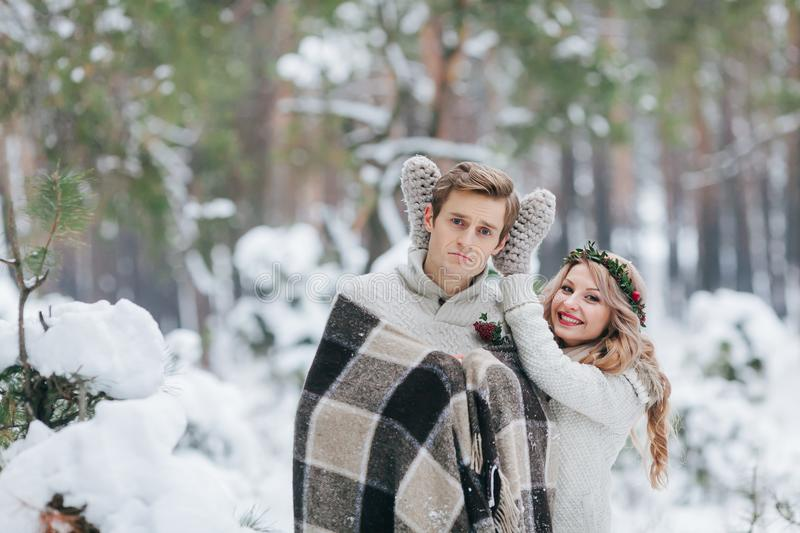 Cute girl covering boyfriend`s eyes by her knitted mittes. Winter wedding. Artwork. stock photography
