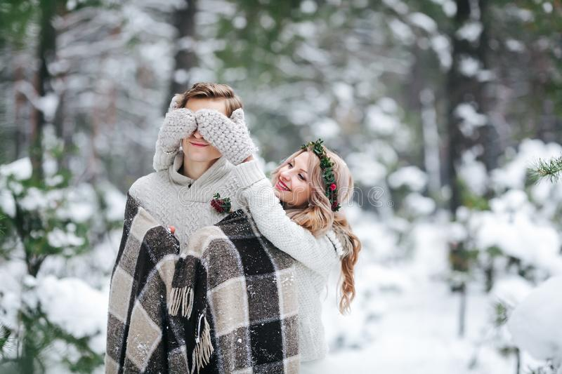 Cute girl covering boyfriend`s eyes by her knitted mittes. Winter wedding. Artwork. stock images