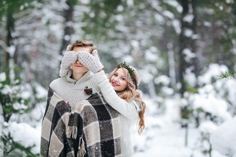 Cute girl covering boyfriend`s eyes by her knitted mittes. Winter wedding. Artwork. stock image