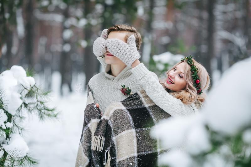 Cute girl covering boyfriend`s eyes by her knitted mittes. Winter wedding. Artwork. royalty free stock photos