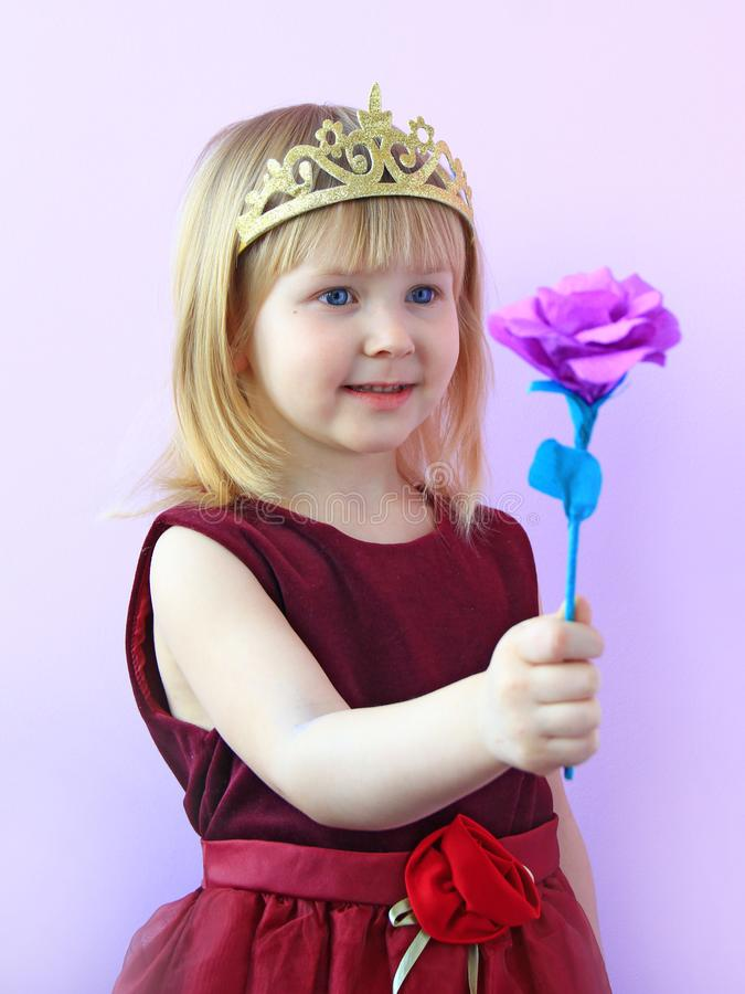 Cute girl with crown on head offering pink rose.Child in beautiful dress smiling stock photography
