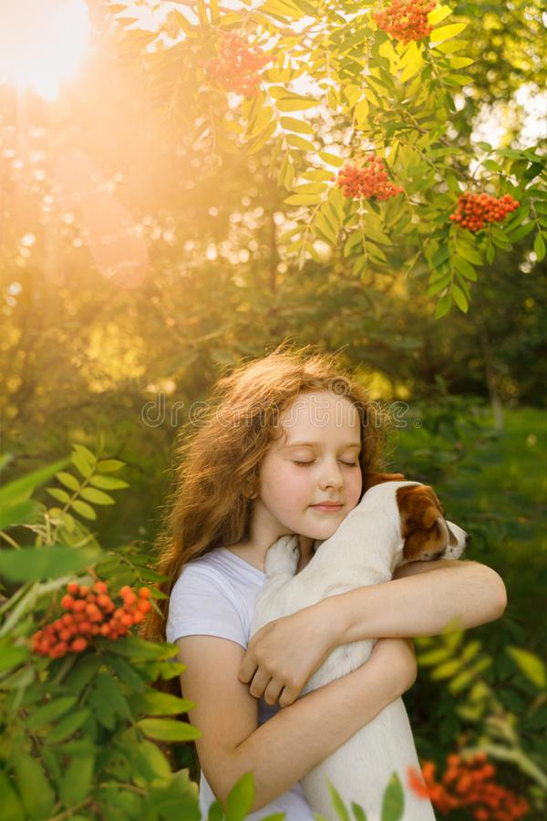 Cute girl with curly hair embraces the puppy royalty free stock image