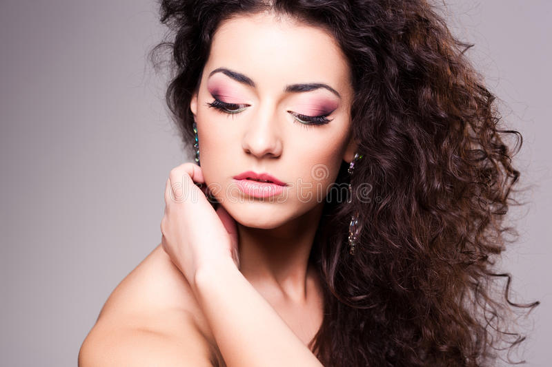 Cute girl with curly hair wearing make-up - studio shot royalty free stock photography
