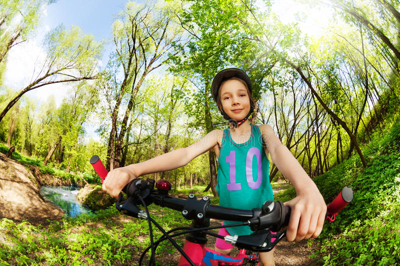 Cute girl cycling by the side of river in woodland. Portrait of young girl in bicycle helmet, cycling by the side of the river in the spring wood royalty free stock photography