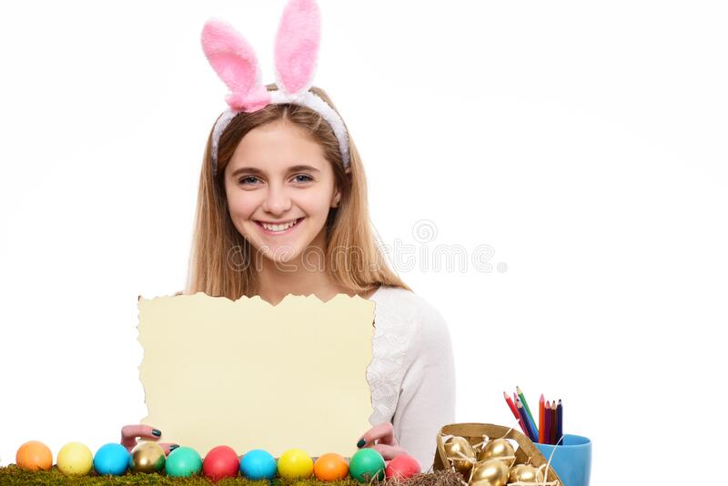 Cute girl with decorated easter eggs isolated at white background. Smiling girl wear bunny ears on Easter day. Young stock photos