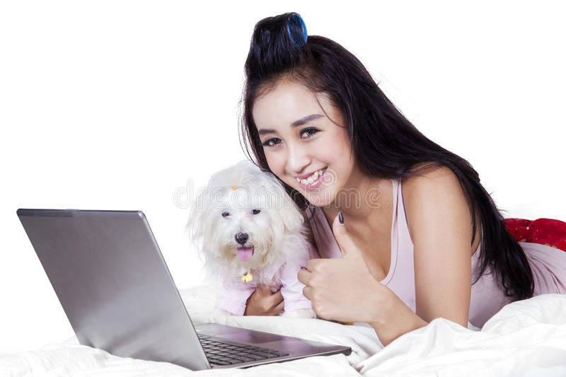 Cute girl with dog showing thumb up. Portrait of excited young woman with dog and laptop, showing thumb up at the camera on the bed royalty free stock photography